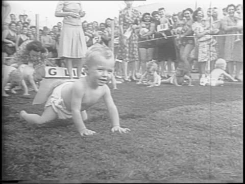 mothers parade around baby race track with babies / a nurse weighs a baby / mothers show their babies to the camera line babies up at the starting... - krabbeln stock-videos und b-roll-filmmaterial