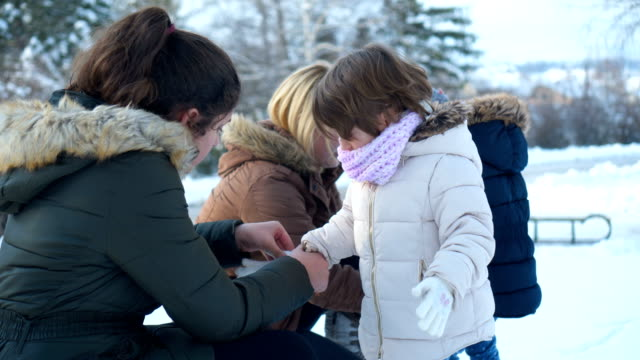 mothers prepare daughters for snow - coat garment stock videos & royalty-free footage