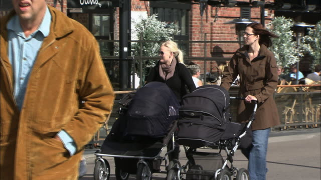 Mothers push their babies in strollers as they pass shops and cafes in Oslo, Norway.