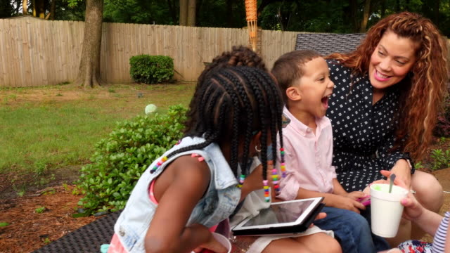 MS Mothers sitting with young kids during backyard party
