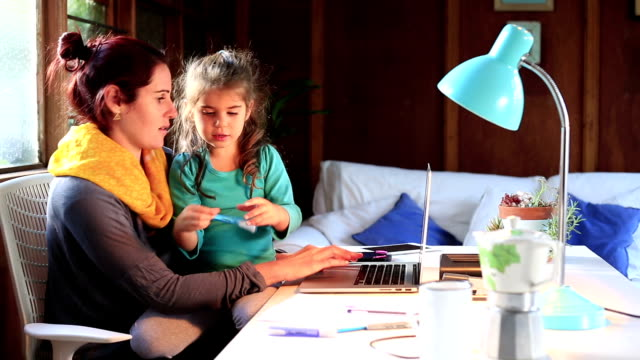 mothers struggles to work while her little girl sits on her lap - working mother stock videos & royalty-free footage