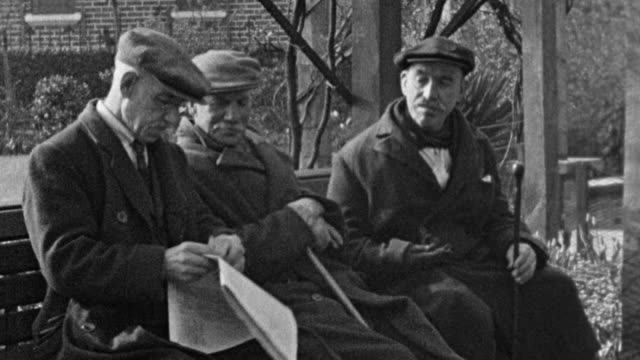vidéos et rushes de 1937 montage mothers walking with children and prams, residents sitting on bench in inner city park, children standing by reflecting pool and playing on playground equipment and slide / london, england, united kingdom - banc