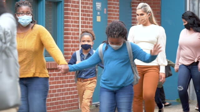 mothers with children, back to school during covid-19 - elementary school building stock videos & royalty-free footage