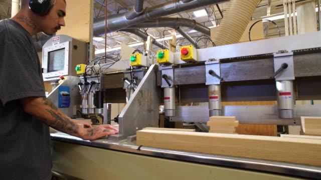 vídeos de stock e filmes b-roll de wa motion control dolly along high-tech, computer-controlled custom wood drill equipment revealing operator - protetor de ouvido