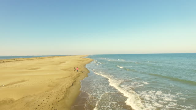 Motion footage recorded with drone of a straight couple in love walking on the beach of Ebro Delta with Mediterranean sea and low waves during travel weekend in the Catalonia region. 4K UHD.