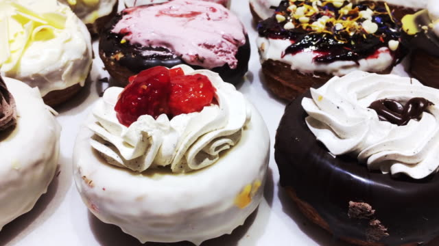 Motion footage recorded with smartphone of colorful and delicious cronuts in bakery pastry store of Barcelona city with tasty and sweet desserts.