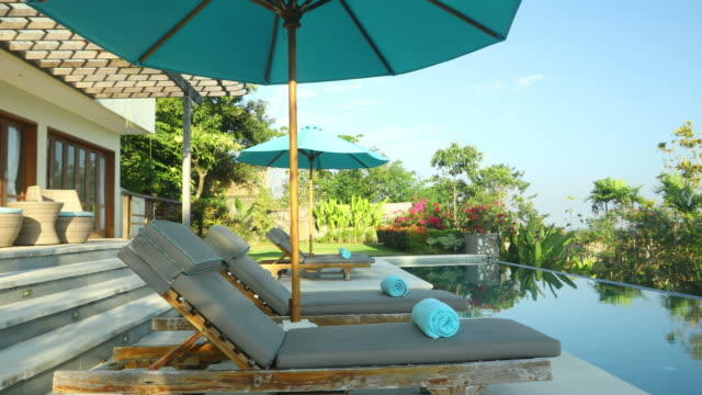 vídeos de stock e filmes b-roll de motion panning of luxurious villa property with swimming pool - bali