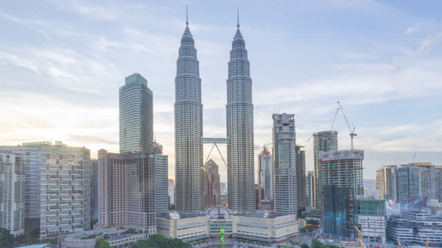 motion panning time lapse of sunset day to night at kuala lumpur city skyline - petronas twin towers stock videos and b-roll footage