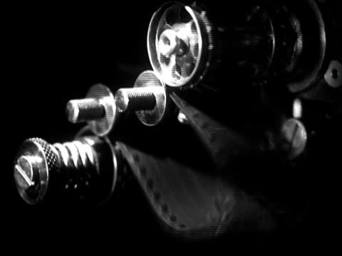 vidéos et rushes de b/w cu 1936 motion picture film movie between sprockets of projector - pellicule photo