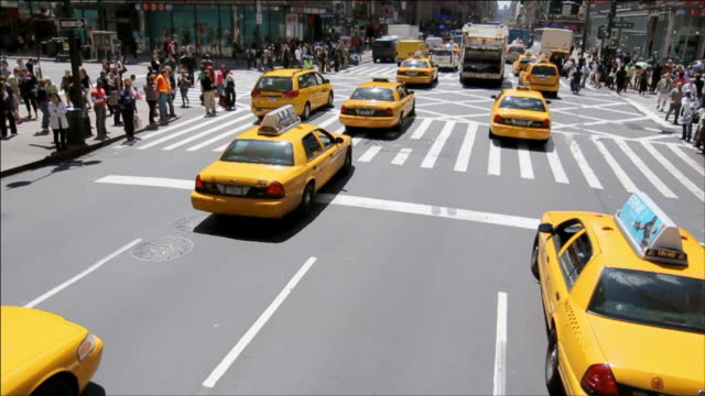 Motion shot of cabs driving trough Manhattan with many pedestrians and policeman