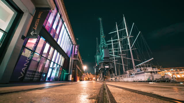 motion time lapse shot of people walking along a dark city street at night, alongside boats and cranes lit by neon lighting on august 03 in bristol,... - blurred motion stock videos & royalty-free footage