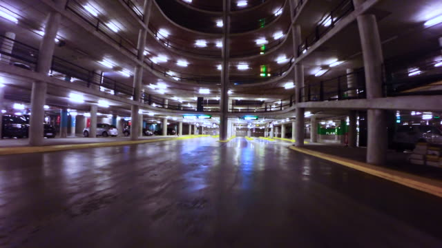Motion video driving through a huge concrete parking with ramps at night.