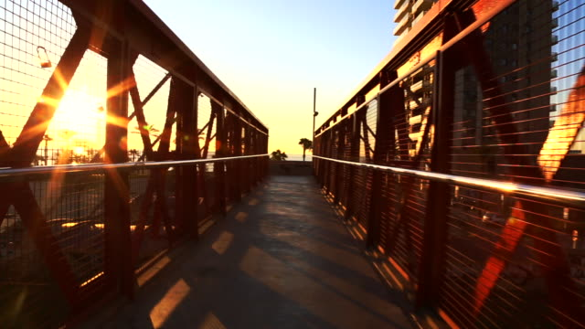 motion view recording nice iron bridge in the barcelona shoreline with cityscape crossing over train railroad during sunrise and beach views. - walking point of view stock videos & royalty-free footage