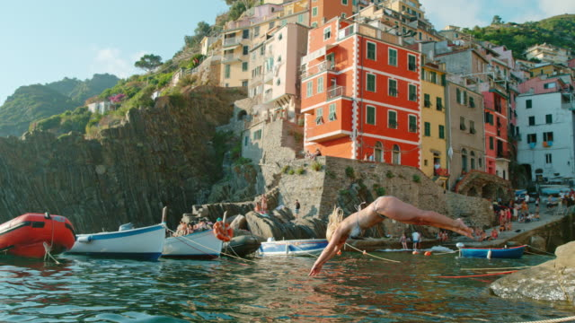 ws time warp effect super slow motion motion young woman jumping into sea, cinque terre, italy - cultura italiana video stock e b–roll