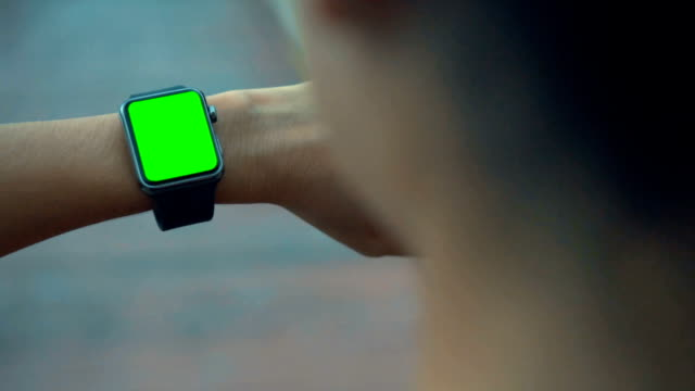 HD SLOW MOTION:Woman jogging and looking at smart watches,Green screen