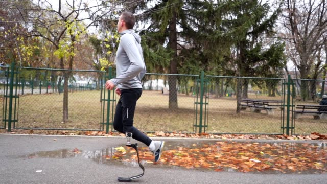 motivated amputee athlete running outdoors after rain - artificial limb stock videos & royalty-free footage