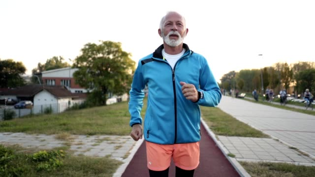 motivated senior man jogging on a running track - uomini anziani video stock e b–roll