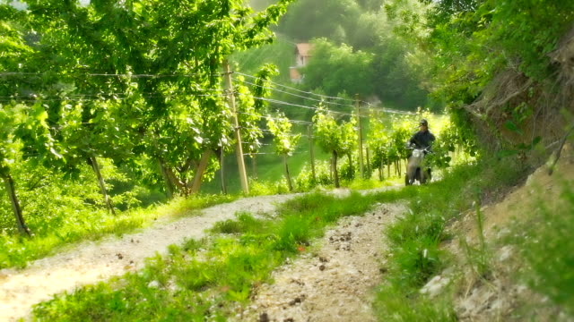 hd slow motion: moto rider on dirt road - moped stock videos and b-roll footage