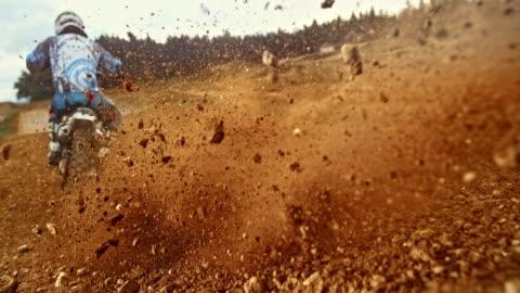 vídeos y material grabado en eventos de stock de slo mo moto de motocross aterrizando en piedras de chorro de grava alrededor - carretera de tierra