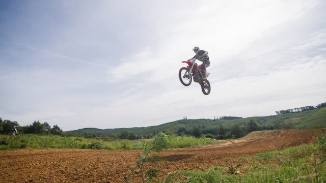 motocross biker jumping on dirt road - 4x4 stock videos and b-roll footage