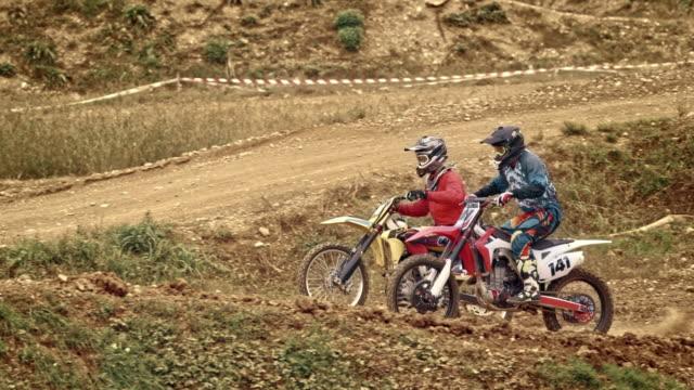 slo mo motocross bikers in a race - gara off road video stock e b–roll