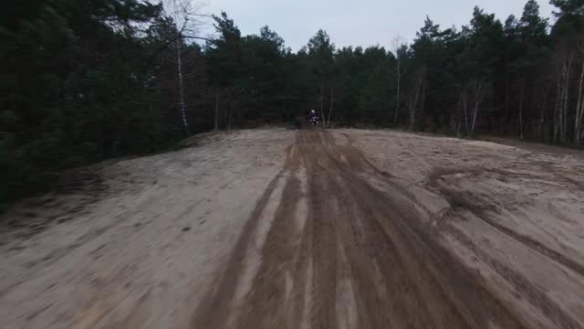 夕暮れ時のモトクロスレース。クロスカントリー地形でスピードを出すドライバー。fpv - レーシングドローンビュー。ドライバーによるパス - クロスカントリーサイクリング点の映像素材/bロール