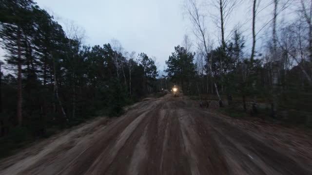 夕暮れ時のモトクロスレース。クロスカントリー地形でスピードを出すドライバー。fpv - レーシングドローンビュー。 - クロスカントリーサイクリング点の映像素材/bロール