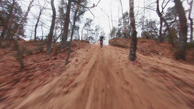 モトクロスレース。クロスカントリー地形でスピードを出すドライバー。fpv - フォレストの上を飛行し、ドライバーに続くレーシングドローンビュー - クロスカントリーサイクリング点の映像素材/bロール