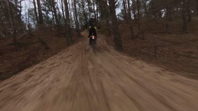 モトクロスレース。クロスカントリー地形でスピードを出すドライバー。fpv - レーシングドローンビュー - クロスカントリーサイクリング点の映像素材/bロール