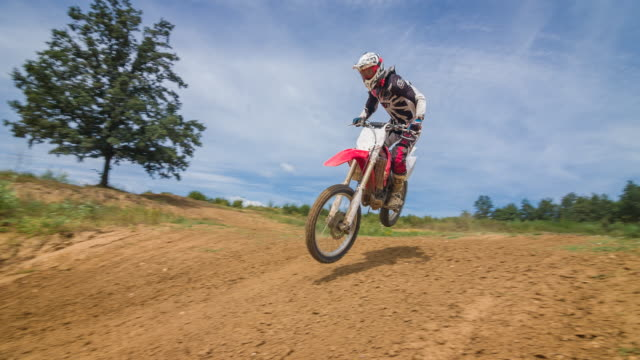 motocross racer jumping on dirt track - gara off road video stock e b–roll