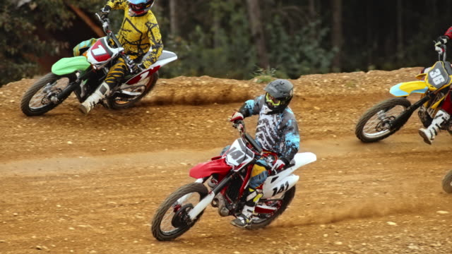 slo mo motocross racers on dirt track - motocross stock videos & royalty-free footage