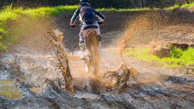 motocross rider driving through a puddle of mud - motorcycle racing stock videos and b-roll footage
