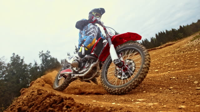 slo mo motocross rider in a turn on dirt trail - motorcycle racing stock videos and b-roll footage