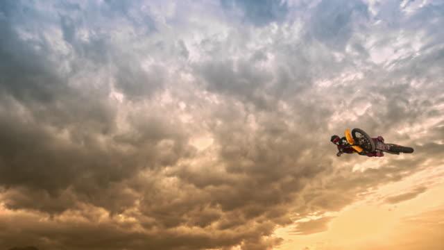 slo mo motocross-fahrer bei sonnenuntergang in der luft - stunt stock-videos und b-roll-filmmaterial