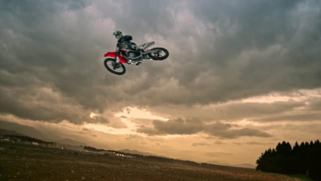 slo mo motocross rider jumping at sunset - motocross stock videos & royalty-free footage