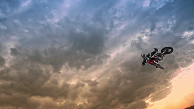 slo mo motocross rider jumping into air at sunset - professional sportsperson stock videos & royalty-free footage