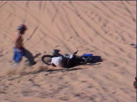 zo, ms, pan, zi, motocross rider jumping over sand dune and crashing, other riders rushing to help him, glamis, california, usa - motocross stock videos & royalty-free footage