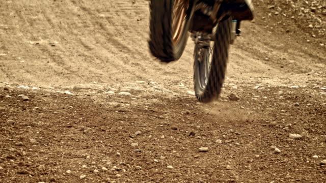 slo mo motocross rider riding bike in dirt - gara off road video stock e b–roll
