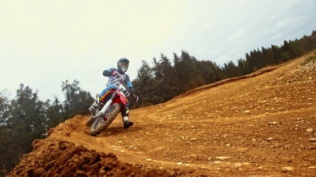 ld motocross rider riding through a turn on dirt trail - motocross stock videos & royalty-free footage