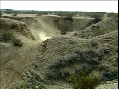 la, composite, ms, shaky, motocross riders jumping off dirt mounds, one crashes and recovers, death valley, california, usa - film composite stock videos & royalty-free footage