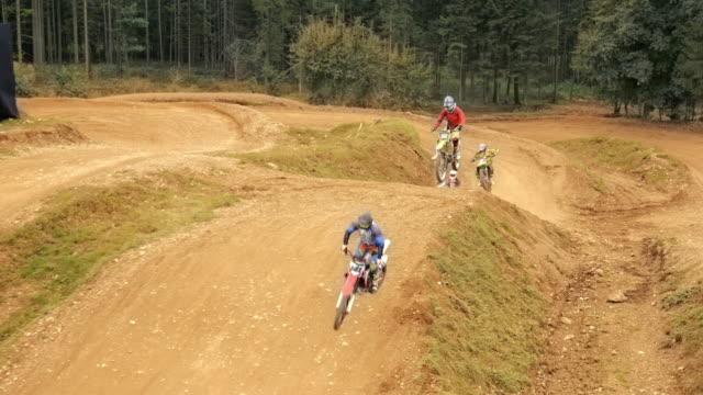 vidéos et rushes de aerial motocross coureurs de course dans le parc de la saleté - monter sur un moyen de transport