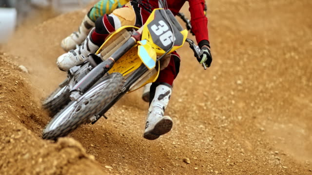 vídeos de stock e filmes b-roll de slo mo motocross riders racing on a dirt track - perícia