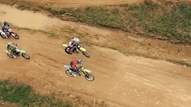aerial motocross riders racing on dirt trail - strada in terra battuta video stock e b–roll
