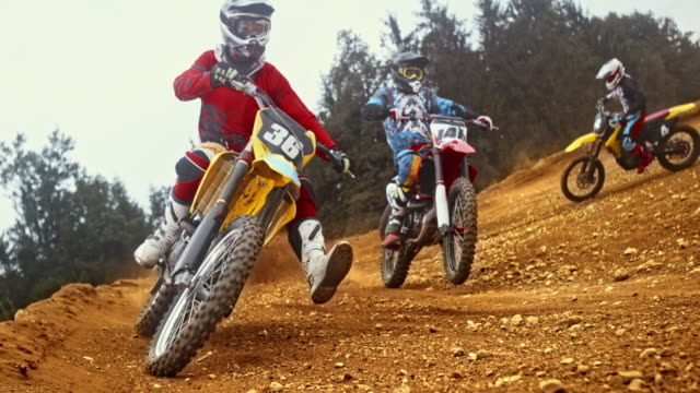 slo mo motocross riders racing through a turn - dirt track stock videos & royalty-free footage