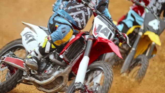 slo mo motocross riders riding on dirt track - motocross stock videos & royalty-free footage
