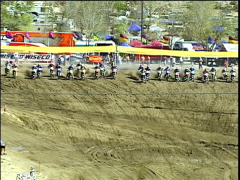 HA, WS, PAN, MS, Motocross riders taking off from starting line, one crashes on turning on dirt track, Glen Helen, California, USA