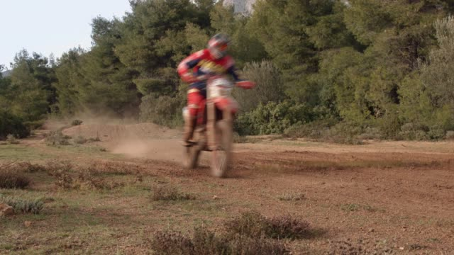 motocross sports and practice at the forest, a motocross athlete is performing a jump with his motorbike, from a perspective view - motorcycle racing stock videos and b-roll footage