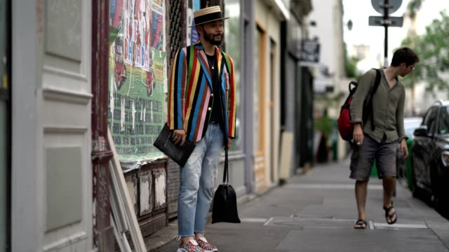 motofumi kogi wearing a multi colored striped jacket, a hat, blue jeans, and sneakers, outside yohji yamamoto during paris fashion week - menswear... - jeans stock videos & royalty-free footage