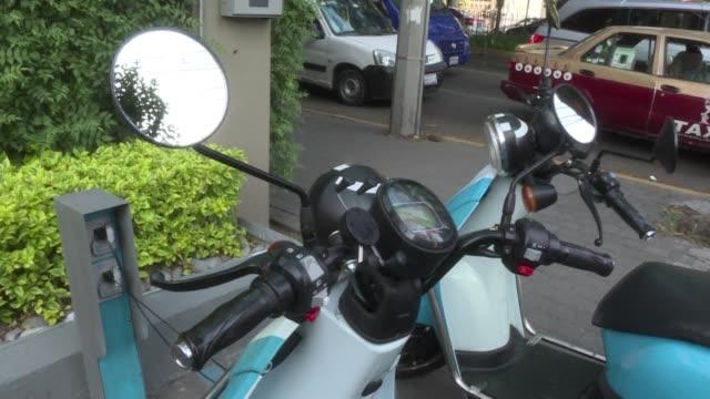 motonetas bicicletas y autos electricos se abren paso en la contaminada ciudad de mexico en alerta ambiental desde hace un mes - transporte bildbanksvideor och videomaterial från bakom kulisserna