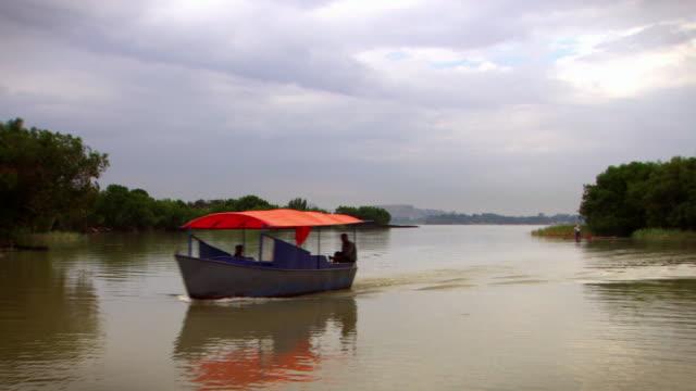 a motor boat moves across the water of lake tana in ethiopia.  - エチオピア点の映像素材/bロール